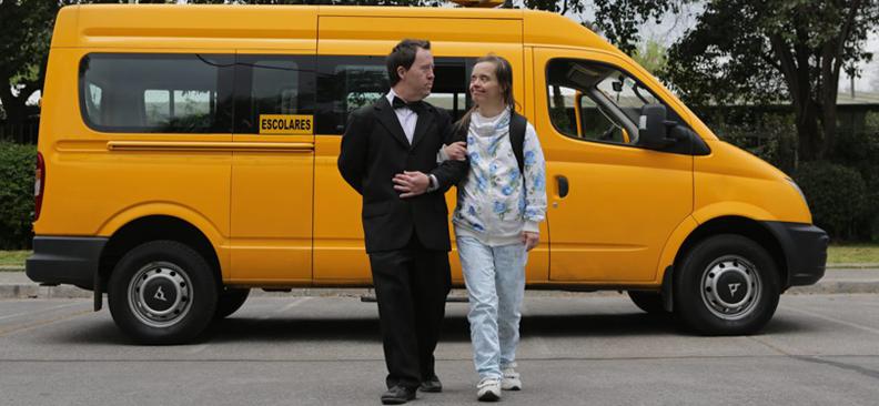 couple souriant qui marche devant le bus jaune