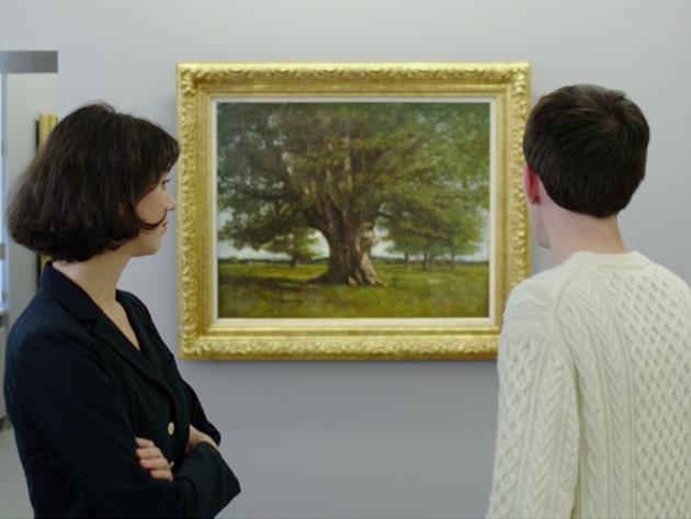 Photo : Au musée, une jeune femme tourne la tête vers Carl, qui est de dos face à la toile Le chêne de Flagey