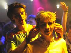 Photo : « David pose un casque de baladeur sur les oreilles d'Alex »