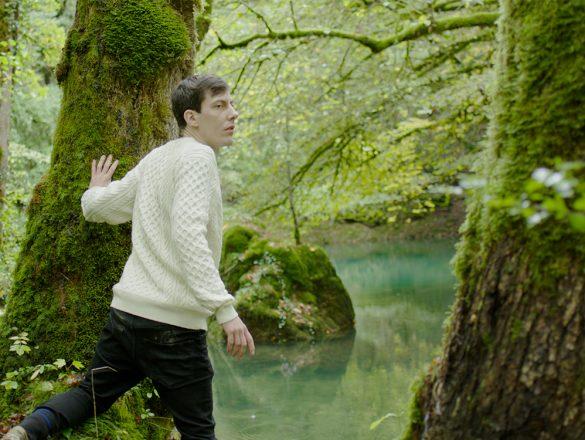 """Photo tirée de """"Quercus"""" : Carl se tient entre deux troncs moussus, face à la rivière calme et transparente"""